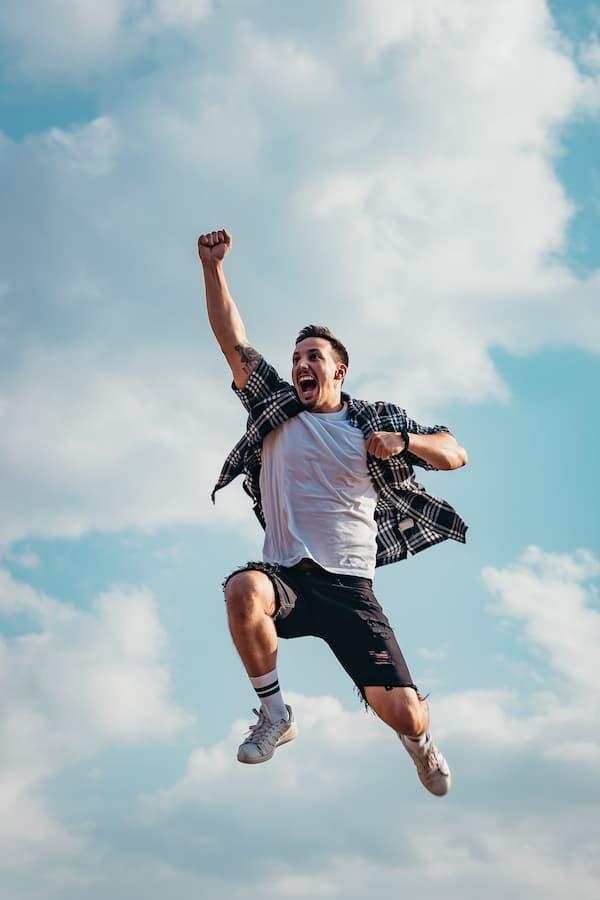 Zdjęcie radosnego młodego mężczyzny natle nieba – wygląda jakby leciał