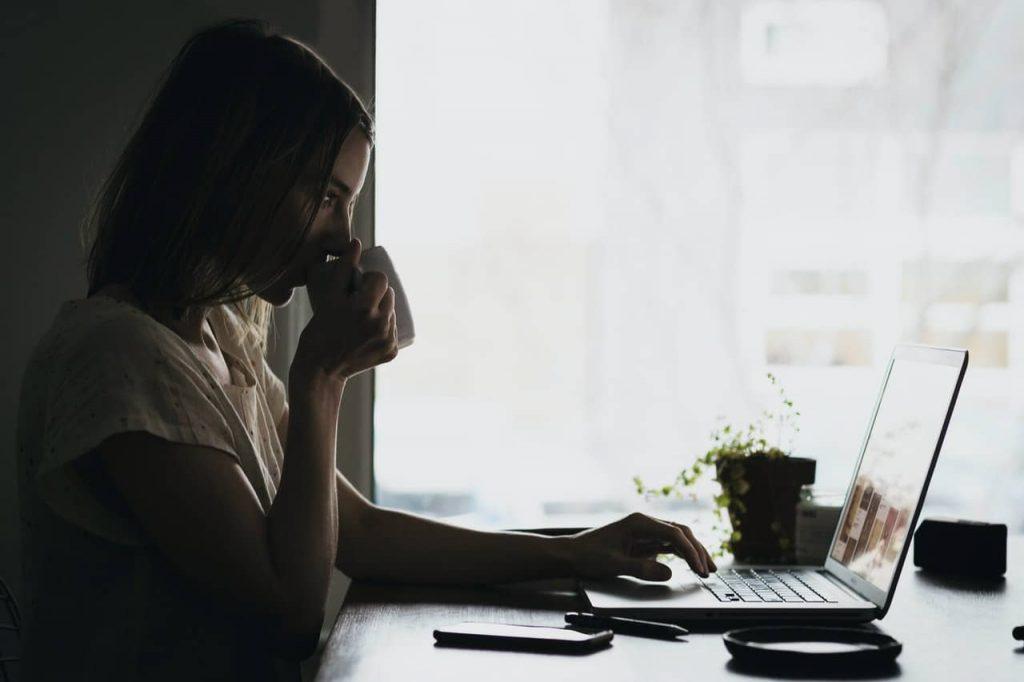 Młoda kobieta pracująca nalaptopie popijając kawę