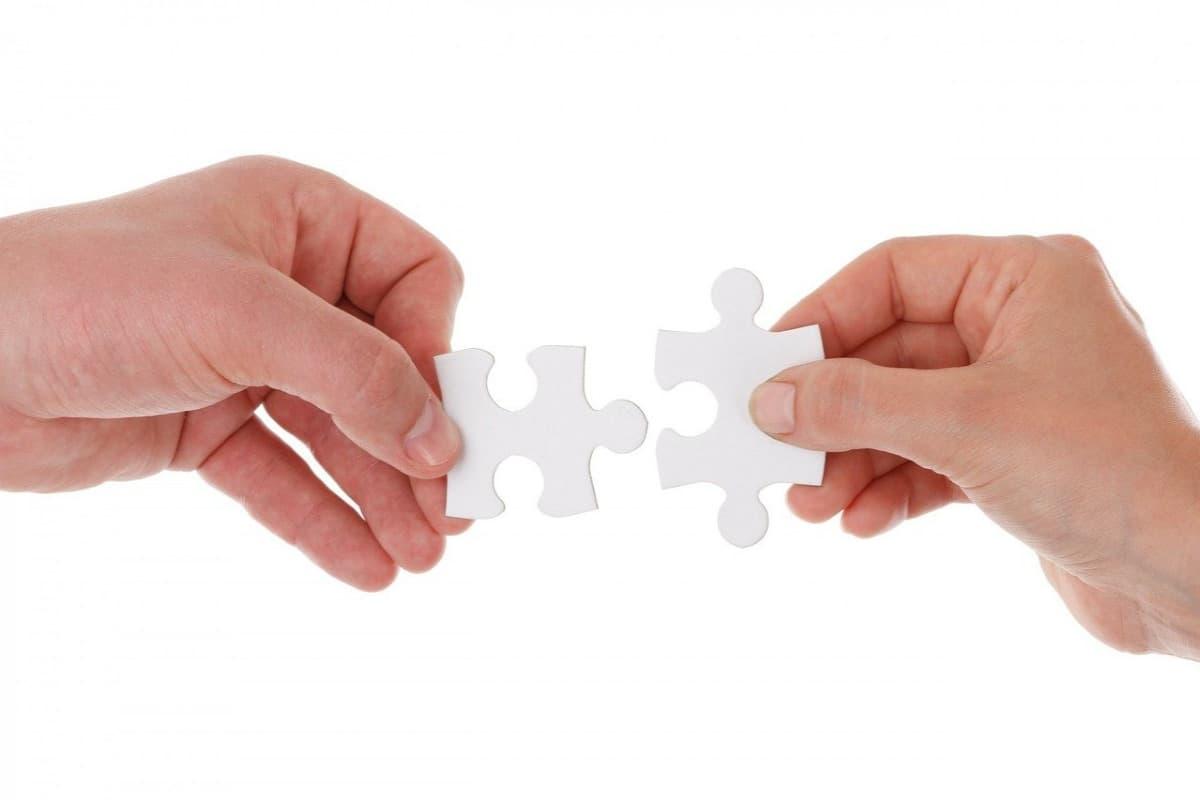 dwie dłonie zbliżające dosiebie pasujące puzzle