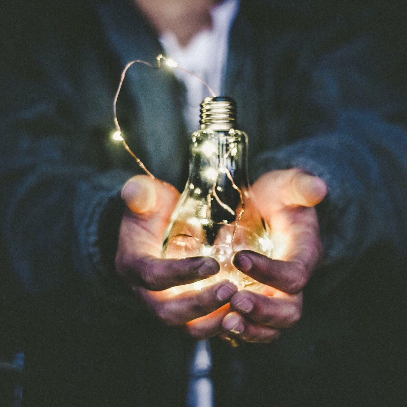 Dłonie trzymające świecącą żarówkę