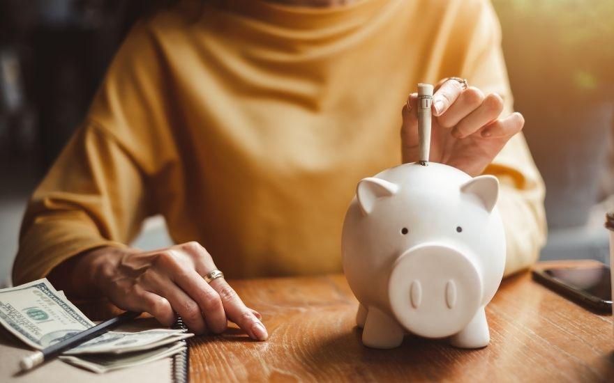 kobieta wkłada banknoty do świnki skarbonki