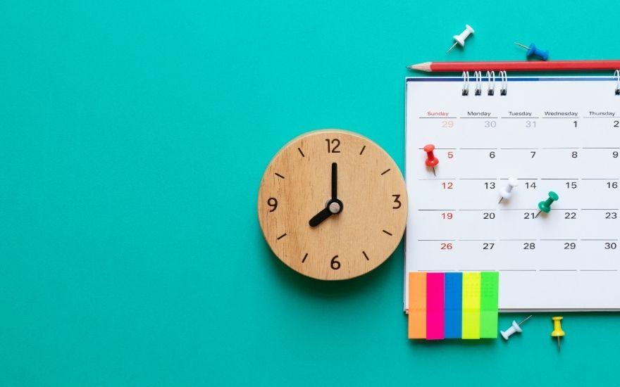 zegar, terminarz i drobne przybory biurowe leżą na biurku