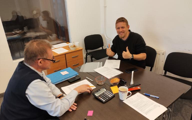 Moment podpisania umowy o dotację z Larigo Group. Uśmiechnięty mężczyzna podnosi kciuki do góry